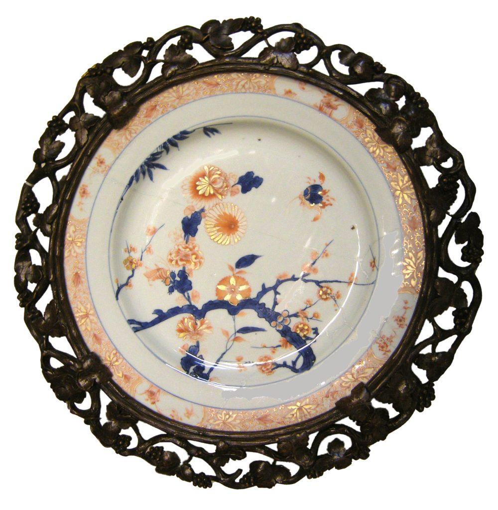 Piatto con decoro Imari cinese e cornice lignea a tralci di vite Cina, dinastia Qing, epoca Kangxi (1662-1722), fine del XVII-inizio del XVIII sec. porcellana, blu di cobalto sotto coperta, smalto rosso e ora sopra coperta; legno intagliato alt. cm 5,5 diam. cm 36,5 (con cornice: alt. cm 6,5 diam. cm 46,5) inv. 30161porcellana, blu di cobalto sotto coperta, smalto rosso e ora sopra coperta; legno intagliato alt. cm 5,5 diam. cm 36,5 (con cornice: alt. cm 6,5 diam. cm 46,5) inv. 30161